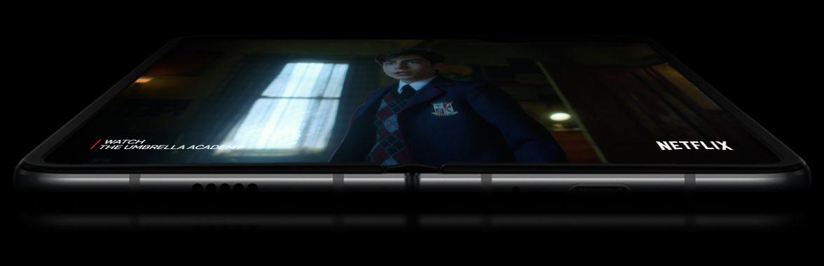 O Galaxy Fold aberto e virado para baixo, com duas baterias a flutuar de cada lado do ecrã. O ecrã aparece no topo com uma cena da série original do Netflix, The Umbrella Academy